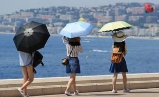 Des promeneurs se protègent du soleil sur le bord de mer à Nice (image d'illustration).