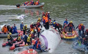 Des équipes de secours tentent de dégager des passagers survivants du crash d'un ATR 72-600 de la TransAsia Airways dans une rivière, le 4 février 2015 près de Taipei
