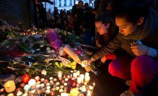 Des personnes déposent des bougies en hommage aux victimes des attentats rue de Charonne à Paris, le 14 novembre 2015