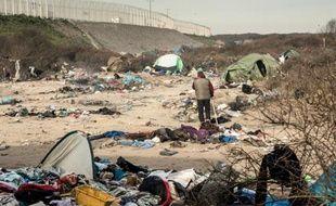 """Un homme marche dans le campement surnommé la """"Jungle"""" à Calais, le 18 janvier 2016"""