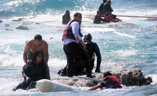 Un homme porte secours à un migrant sur l'île de Rhodes, en Grèce, le 20 avril 2015.