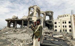 Un milicien Houthi pose devant une maison détruite par un bombardement aérien, le 29 mai 2015 à Sanaa