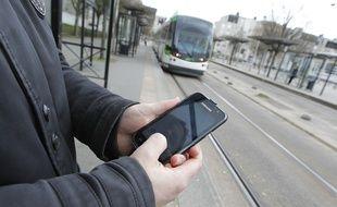 Un homme consulte son téléphone portable à Nantes (illustration).