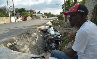 Une voiture percutée par le bus gît dans un fossé près de Port-au-Prince, le 12 mars 2017.