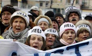 """Des manifestants pro-UE le 20 janvier 2014, avec des bandeaux portant le message """"help"""", à l'aide, devant la délégation européenne à Kiev en Ukraine"""
