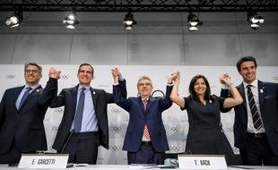 Los Angeles (à gauche) et Paris (à droite) entourant Thomas Bach, président du CIO