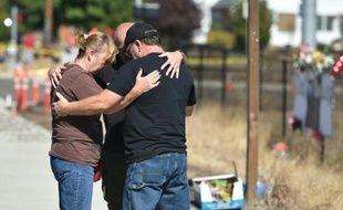 Des gens prient près de l'entrée de l'université d'Umpqua à Roseburg (Etats-Unis), dans l'Oregon, le 3 octobre 2015, quelques jours après le meurtre de dix personnes par un homme armé