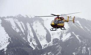 Un hélicoptère de la sécurité civile survole le lieu du crash d'un Airbus A320 qui à fait 150 morts dans les Alpes françaises, le 24 mars 2015
