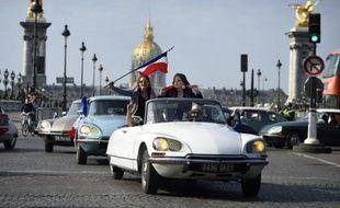 Les occupants d'une DS agitent le drapeau français près du pont Alexandre III à Paris le 24 mai 2015 pour célébrer le 60e anniversaire de la voiture mythique de Citroën