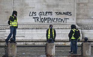 Des «gilets jaunes» posent devant le tag inscrit sur l'arc de Triomphe, à Paris, le 1er décembre.