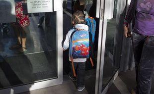 Un enfant à la porte de son école primaire, à Saint-Ouen (Seine-Saint-Denis), le 3 septembre 2013