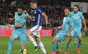 Le milieu de terrain français de Strasbourg Jonas Martin affronte le défenseur français de l'Olympique de Marseille Adil Rami, lors du match entre Strasbourg (RCSA) et Marseille (OM), le 3 mai 2019, au stade Meinau de Strasbourg.