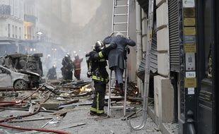 Un pompier vient en aide à une personne âgée après l'explosion due au gaz rue de Trévise (9e) à Paris, le 12 janvier 2019.