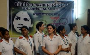 Des infirmières indiennes devant le portrait d'Aruna Shanbaug à l'hôpital de Mumbai le 18 mai 2015.AFP PHOTO/ PUNIT PARANJPE