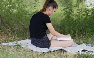 Une adolescente qui lit en vacances.