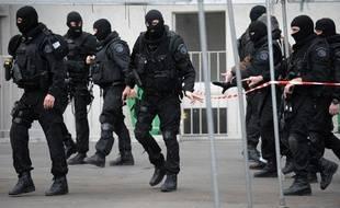 Des policiers de la brigade de recherche et d'intervention (BRI) marchent dans la rue le 09 mars 2009 à Paris, après leur intervention dans un immeuble au 51 de la rue Auguste Blanqui (XIII), où un homme armé s'était retranché dans son appartement aprés avoir blessé par balles un homme sur la voie publique à la hauteur du métro Corvisart.