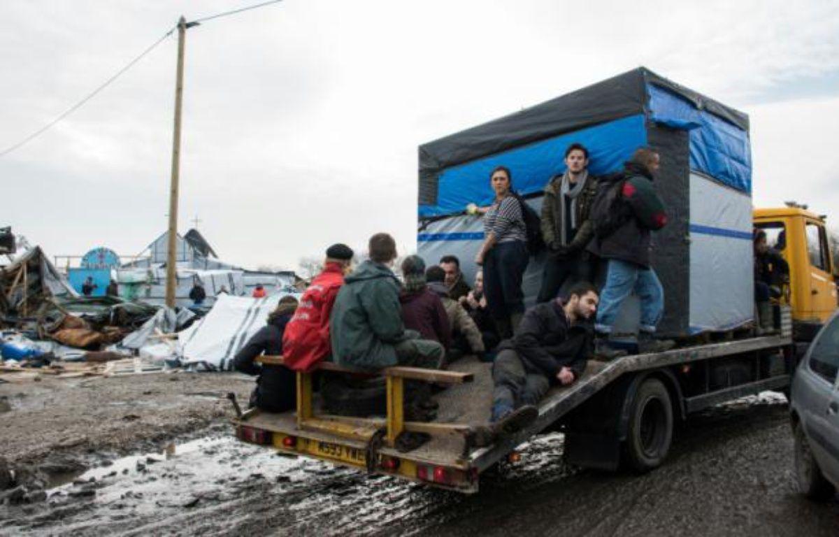 """Des migrants quittent la zone sud de la """"Jungle"""" lors de son démantèlement le 10 mars à Calais – DENIS CHARLET AFP"""