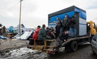 """Des migrants quittent la zone sud de la """"Jungle"""" lors de son démantèlement le 10 mars à Calais"""