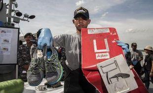 """Un responsable indonésien montre le 5 janvier 2015 des débris de l'avion d'AirAsia qui s'est écrasé en mer, ainsi qu""""une paire de chaussures récupérée sur les lieux"""