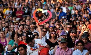 Une femme brandit un coeur lors d'un rassemblement de POdemos à Alicante le 17 juin 2016