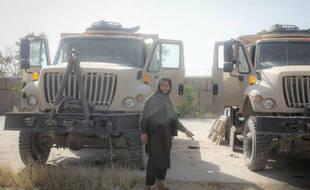 Un combattant taliban pose avec des véhicules et des équipements militaires capturés par les talibans à Gardiz le 12 août 2021.