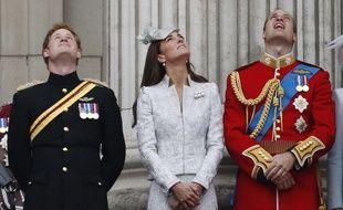 Kate Middleton, entouré des princes Harry et William, son époux, regarde la Royal Air Force survoler Buckingham Palace, le 14 juin 2014.