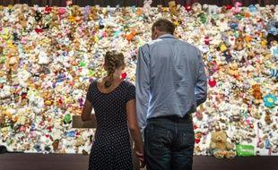 """Un couple se recueille devant une """"haie de la compassion"""" constituée de milliers de peluches à Nieuwegein, près d'Utrecht, le 17 juillet 2015, avant une cérémonie en hommage aux victimes du crash du vol MH17 de la Malaysian Airlines en Ukraine"""