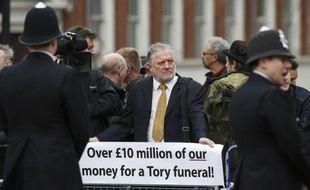 """""""Maggie, pourrie,"""" crient des manifestants, en tournant le dos au passage du cercueil de Margaret Thatcher drapé dans l'Union Jack. Sur le trottoir d'en face, des vétérans des Malouines, béret rouge et médailles fièrement accrochées à leur veste, applaudissent spontanément le cortège tiré par des chevaux noirs."""