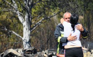 Une habitante de Bormes-les-Mimosas (Var) est réconfortée par un sapeur-pompier, ce 26 juillet 2017, alors que la commune et ses alentours étaient menacés par des incendies.