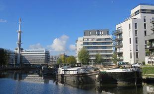 Vue des péniches et de l'immeuble de bureaux La Mabilais depuis les berges de la Vilaine à Rennes.