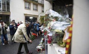 Un homme dépose des fleurs devant le siège de Charlie Hebdo à Paris le 8 janvier 2015