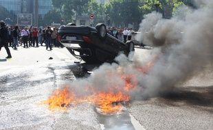 Une voiture brûle pendant une manifestation de taxis anti-Uber, le 25 juin 2015, à Paris (porte Maillot).