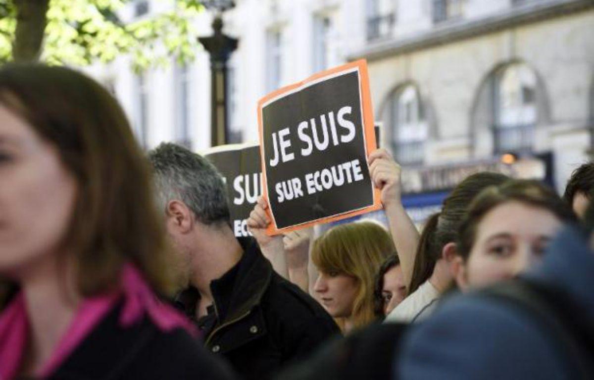 """Des manifestants portent des pancartes """"Je suis sur écoute"""" pastichant le slogan """"Je suis Charlie"""" pour protester contre le projet de loi sur le renseignement, le 13 avril 2015 à Paris – Eric Feferberg AFP"""