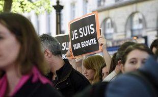 """Des manifestants portent des pancartes """"Je suis sur écoute"""" pastichant le slogan """"Je suis Charlie"""" pour protester contre le projet de loi sur le renseignement, le 13 avril 2015 à Paris"""