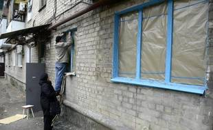 Un homme répare les fenêtres d'un logement le 13 novembre 2014 à Donetsk