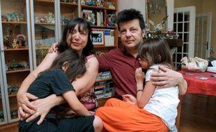Sylvie et Dominique Mennesson, parents de jumelles nées en 2000 d'une mère porteuse californienne, posent avec leurs filles, le 2 juillet 2009 dans leur maison de Maison-Alfort