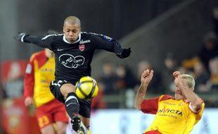 Le Valenciennois Mathieu Dossevi taclé par le Lensois, Yohan Demont, le 5 février 2011 à Lens.