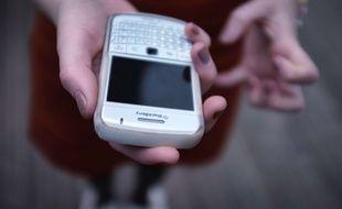 Une femme consulte sa messagerie électronique sur son smartphone.