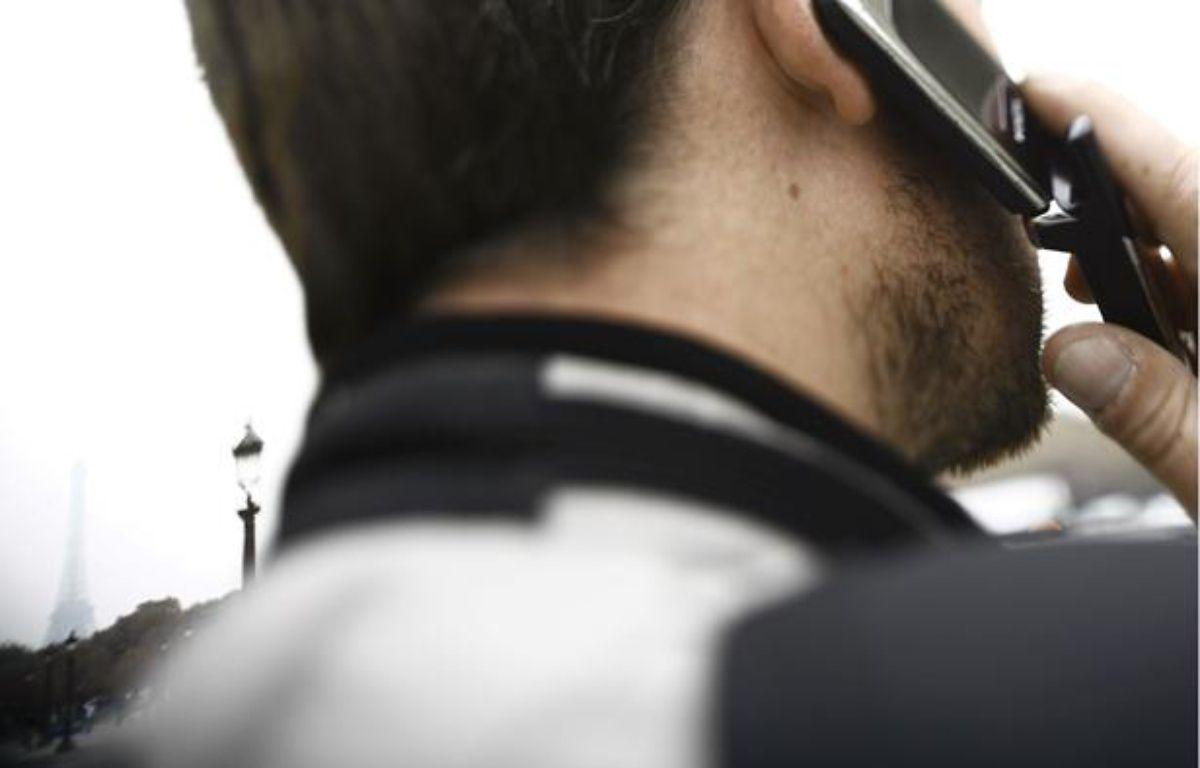 Une personne utilise son téléphone portable, le 15 septembre 2006 place de la Concorde à Paris. – AFP PHOTO/FRED DUFOUR