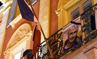 "The image of mountain-guide Herve Gourdel, is placed on the balcony of the town hall on September 24, 2014, in Saint-Martin-Vésubie, following his beheading by Jihadists linked to the Islamic State group in Algeria. Jund al-Khilifa, or ""Soldiers of the Caliphate,"" beheaded the 55-year-old Frenchman who was abducted on September 21 while hiking in a national park that was once a magnet for tourists but later became a sanctuary for Islamists. AFP PHOTO / ANNE-CHRISTINE POUJOULAT"