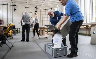Des volontaires vident l'urne d'un bureau de vote de Zurich, en Suisse, le 20 octobre 2019.
