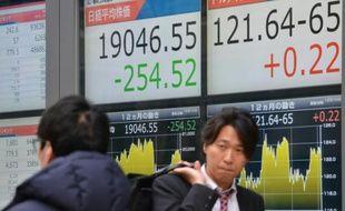 Des piétons passent devant des tableaux indiquant les cours de la Bourse, à Tokyo le 10 décembre 2015