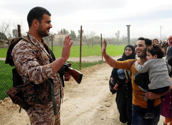 DAMASCUS, March 15, 2018 (Xinhua) -- A civilian greets a Syrian soldier while evacuating the town of Hamouriyeh in Eastern Ghouta area of Damascus, Syria, March 15, 2018. The Syrian army captured the Hamouriyeh district in the capital Damascus' Eastern Ghouta countryside after the withdrawal of the Failaq al-Rahman rebel group as 12,500 people evacuated that area on Thursday, a monitor group reported. (Xinhua/Ammar Safarjalani) - Ammar Safarjalani NOUVELLE/SIPA/1803160900