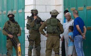 Des soldats israéliens interrogent des Palestiniens le 17 juin à Hebron, dans le cadre de l'enquête pour rechercher trois jeunes israéliens disparus depuis 6 jours