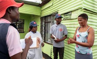 Les membres de la Croix-Rouge internationale fournissent des conseils de prévention pour contenir l'épidémie de coronavirus COVID-19, dans le quartier informel de Protea à Soweto, le 23 mars 2020.