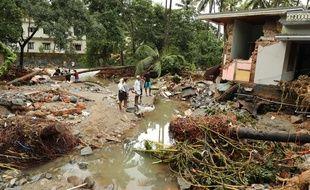 Des habitants observent les dégâts causés par les crues à Kannappankundu, dans l'Etat du Kerala, vendredi 10 août.