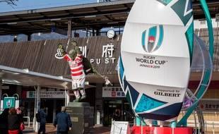 Des touristes se prennent en photo devant un ballon de rugby géant et une statue vêtue d'un maillot de rugby à Beppu, à quelques kilomètres d'Oita.