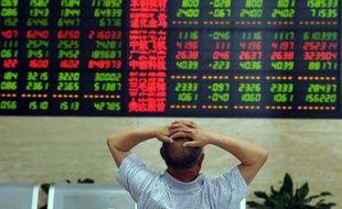 Un investisseur chinois scrute un tableau électronique avec les cours de la bourse de Shanghaï, le 19 juin 2015