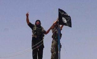 Photo d'archive extraite du compte twitter jihadiste Al-Baraka news le 11 juin 2014 montrant des militants de l'EI et leur drapeau noir sur un fort situé entre la province irakienne de Ninive et la ville syrienne de Al-Hasakah