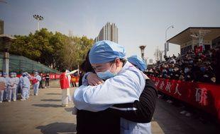 A droite, un soignant de Wuhan serre dans ses bras un compatriote de la province de Jiangsu venu les aider pendant la crise, le 19 mars 2020.